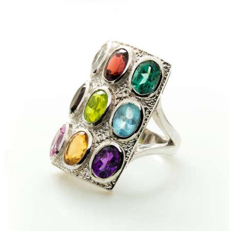 zafiro: Anillo con la piedra preciosa de color differet en el fondo de la pizca