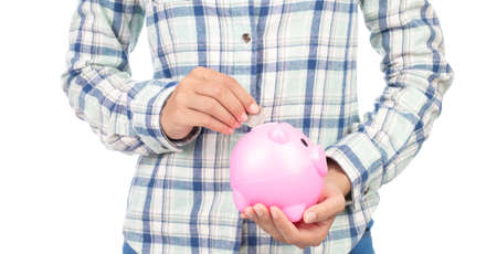 Portrait of girl in plaid shirt holding a piggybank isolated on white background.