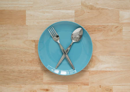 ceramic dish with fork and spoon wood background Фото со стока