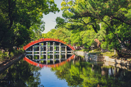Red curve Bridge and reflection in the river with beautiful nature Stock Photo
