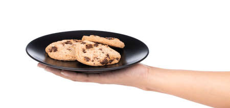 hand holding cookies Chocolate biscuits on dish isolated on white background