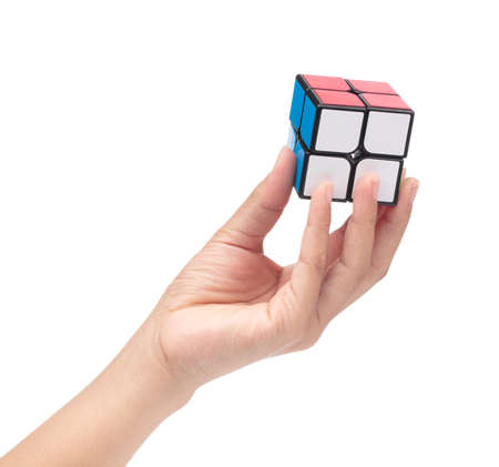 Thailand, Ubon Ratchathani. October 19, 2017. Hand holding Rubik's cube isolated on a white background.  Rubik's Cube invented by a Hungarian architect Erno Rubik in 1974. Editorial