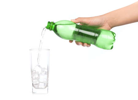 lose up of Hand Pouring aerated soft drink Into Bottle Glass