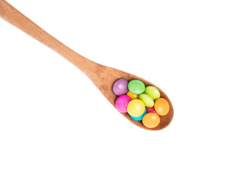 colorful chocolate coated candy on spoon isolated on white background