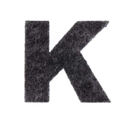 Alphabet K is made of felt isolated on white background.