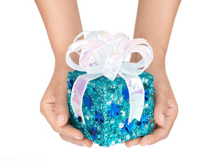 Hand holding blue gift box with ribbon isolated on white background