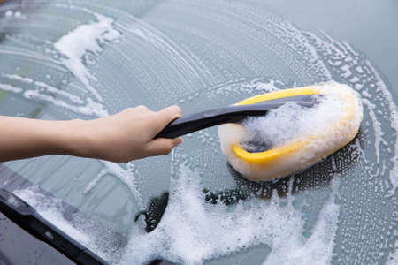 cleaning windscreen of a car with yellow sponge foam.