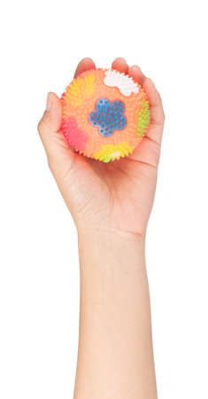 Hand holding Massage Rubber Ball with Spikes isolated on a white background Imagens