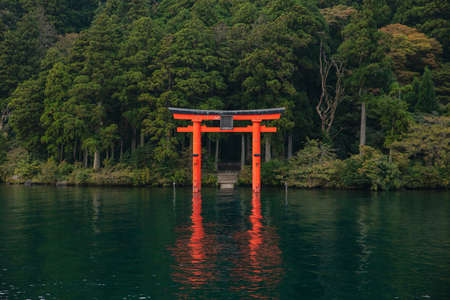 Red Torii gate submerged in the waters of Ashi lake, caldera with mountains on the background