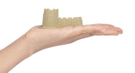 Hand holding sand sculpture of castle isolated on a white background