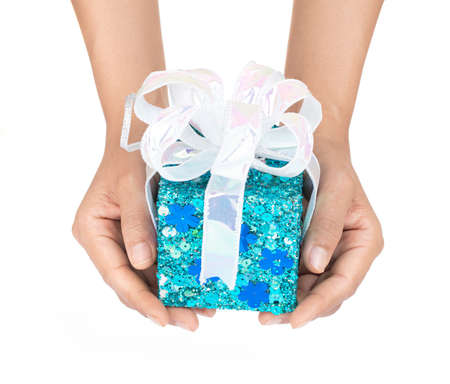 Hand holding blue gift box with ribbon isolated on white background Imagens - 124889629