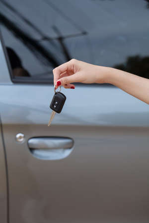 Hand holding car keys with car on background Imagens - 124889632