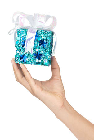 Hand holding blue gift box with ribbon isolated on white background Imagens - 124889644