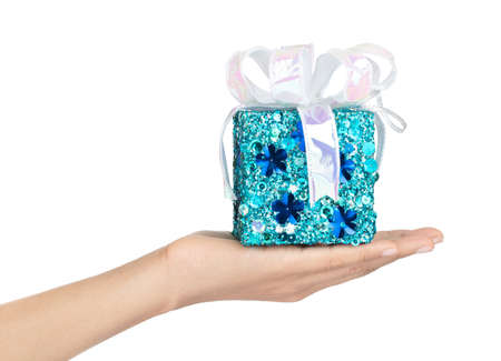 Hand holding blue gift box with ribbon isolated on white background Imagens - 124889645