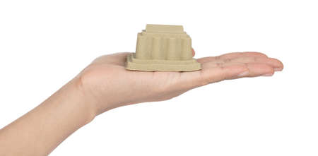 Hand holding sand sculpture of castle isolated on a white background Imagens - 124889649