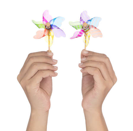 Hand holding two colorful pinwheel isolated on white background 写真素材