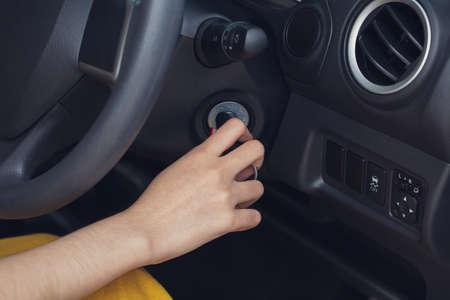 Main de femme démarrant un moteur de voiture avec clé de contact gros plan