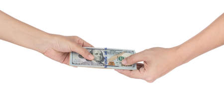 Handing over stacks of cash to other hand isolated on white background.