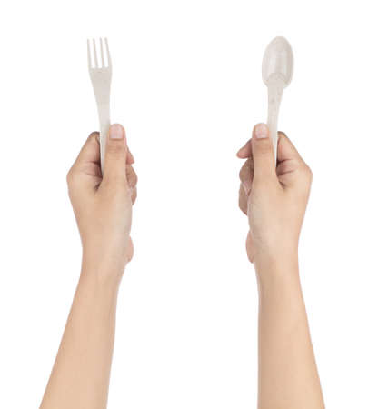 Hand holding Biodegradable plastic spoon and fork isolated on white background