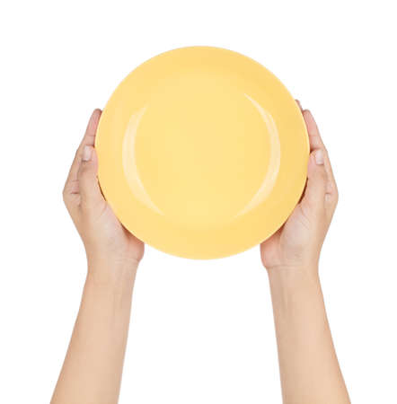 Hand holding Empty yellow plastic plate isolated on white background Imagens