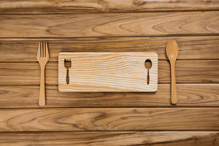 spoon and fork on pale table wood background