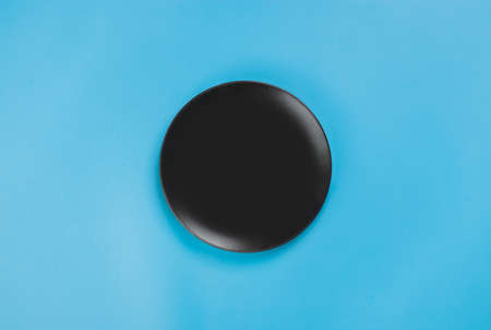 A black plate on blue background Imagens