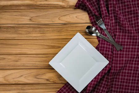 A white plate rests on checkered tablecloth. There are spoon and fork on wood background