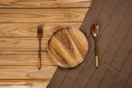 A wood plate rests on a brown cloth. There are spoon and fork on wood background
