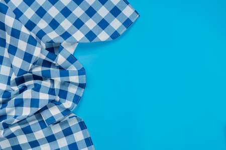 Blue checkered tablecloth on blue background