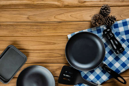 Collection frying pans with checkered tablecloth on wooden background