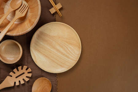 Wooden Kitchenware set with brown tablecloth on brown background Imagens
