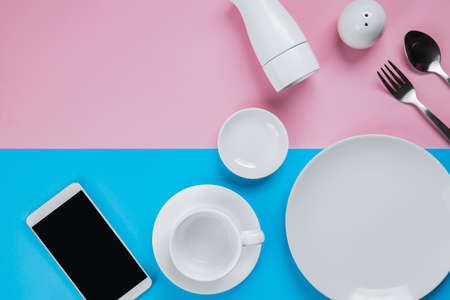 Collection of kitchenware with Smartphone on pink and blue background