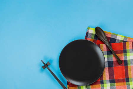 Set black plate with spoon and chopsticks on blue background