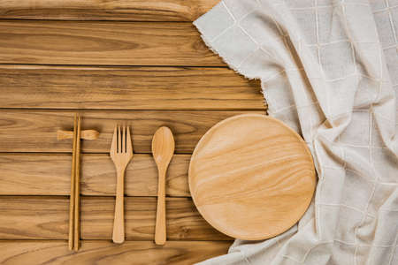 A wood plate rests on a white cloth. There are spoon, fork and chopsticks on wood background