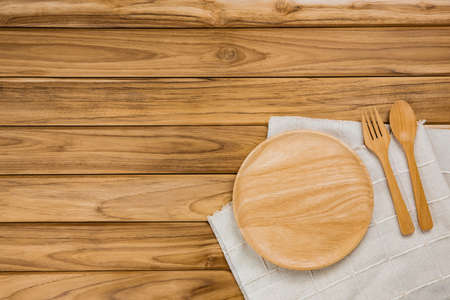 A wood plate rests on a white cloth. There are spoon and fork on wood background