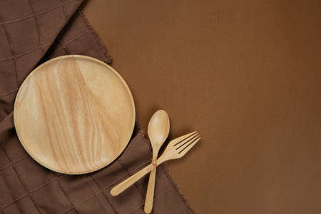 Kitchenware set with brown tablecloth on brown background