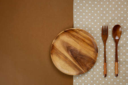 Wooden Kitchenware set with brown tablecloth on brown background