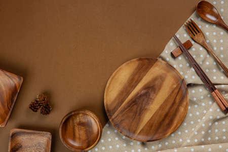 Wooden Kitchenware set with brown tablecloth on brown background Stock Photo