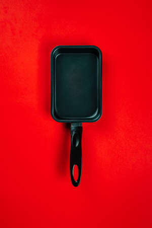 Black frying pans on red background
