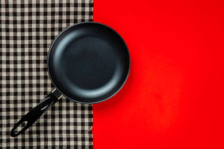 Kitchenware set with black checkered tablecloth on red background Imagens