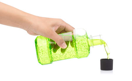 Hand pouring water mouthwash from bottle in to cap isolated on white background Zdjęcie Seryjne