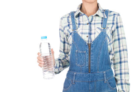 young woman in plaid shirt and bib jeans holding bottle water isolated on white background
