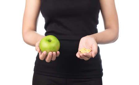 Young slim woman holding green apple. Isolated on white background. Concept of healthy food and the control of excess weight. Foto de archivo