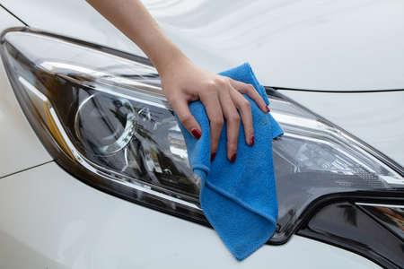 Hand with cloth washing a car.