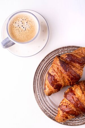 Croissants and a cup of coffee on a white wooden table. Morning still life. Top view with space for text. Flat lay composition. Background for restaurant, bakery, cafe.