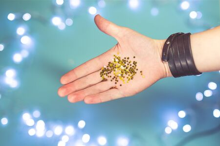 Shiny tiny golden stars in open human palms on a blue background with bokeh. Festive decor, Christmas, New Year. Stock Photo