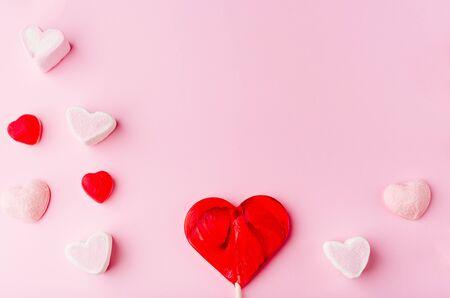 Różowe romantyczne tło wakacje ze słodkimi cukierkami w kształcie serca. Ozdobna karta na Walentynki z miejscem na tekst. Motyw miłości.