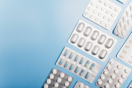 Many different packs of pills on a light blue background. Copyspace. Orthogonal composition. Archivio Fotografico