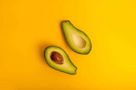 Ripe juicy halved  avocado on a yellow solid background with copy space. Vegan, vegetarian, raw organic food template. Eco detox style. Archivio Fotografico
