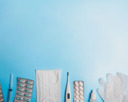 Composition with medical mask, thermometer, syringe, pills and gloves on a blue background. Copyspace.